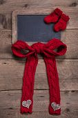 Chalk board with red knitted sock and bow on wooden background