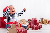 First Christmas: baby unwrapping a present - happy children eyes