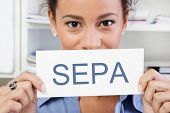 Young woman looking at camera holding a SEPA sign isolated on white background