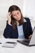 Burnout: overworked tired businesswoman in blue scratching head at desk with laptop and calculator