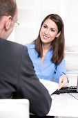 Happy businesswoman in a blue blouse in interview or meeting with a man also as consultant for a ins