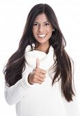 Young beautiful smiling woman isolated on a white background with a with pullover, long black hair and thumbs up.