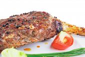 meat over white : grilled meat shoulder on plate with tomatoes green lettuce and cutlery isolated on white background