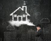 Businessman Thinking About House Shape Cloud With Doodles Wall