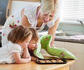 stock photo of mother child  - Smiling woman baking cookies with her daughters in kitchen - JPG