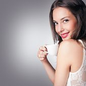 Brunette woman with a cup of gourmet coffee.