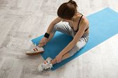 Young sports woman sitting on the yoga mat at gym
