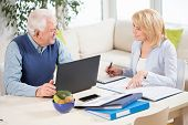 stock photo of fill  - Two elderly businesspeople filling in the documents - JPG