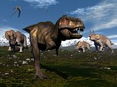 stock photo of pterodactyl  - Tyrannosaurus rex attacked by three triceratops dinosaurs in the mountain  - JPG