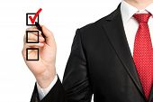 Isolated Businessman In A Suit Holding A Pen And Writing Red Check Mark Or Make A Choice