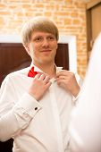 Portrait Of Handsome Young Man Putting On Red Bow Tie