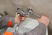 Plumber Fixing Faucet In A Bathroom