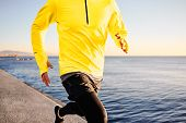 Running Man - Male Runner Training Outdoors Athlete On Beautiful Sunset Or Morning At Beach.
