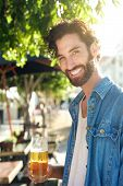 Man Smiling With Refreshing Beer At Outdoor Bar In Summer