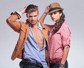 Portrait of a young casual couple posing on studio background, The man is fixing his hair while the woman is leaning on him.