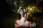 image of night gown  - Young brunette woman sitting at garden at night and holding old lantern - JPG