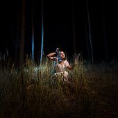 pic of nightgown  - Young woman in nightgown sitting in high forest at night with lantern - JPG