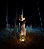 foto of nightgown  - Mysterious shot of beautiful woman in nightgown reading big magical book at dark forest - JPG