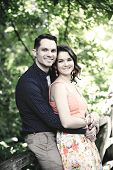 Instagram look of an image showing a happy young couple embracing on a bridge in a wooded setting