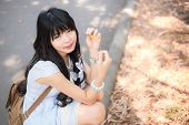 A Cute Asian Thai Girl Is Holding A Dry Leaf And Making Eye Contact
