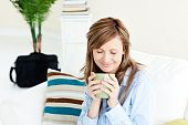 Relaxed Businesswoman Enjoying Her Coffee Sitting On A Sofa