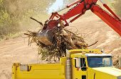 image of excavator  - Track hoe excavator filling up a dump truck at a new commercial construction development - JPG