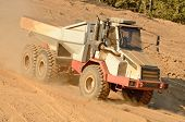 stock photo of dump_truck  - A large articulated dump truck moves top soil pile for later use on a new commercial construction development project - JPG