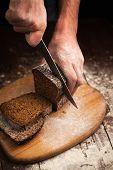stock photo of fresh slice bread  - Male hands slicing fresh bread on wood table  - JPG
