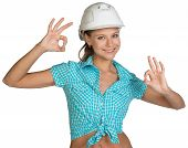 Pretty girl in shirt and white helmet showing ok hand signs. Full length