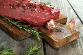 Raw beef steak with rosemary and garlic on cutting board on wooden background