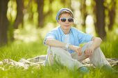 Portrait of cute lad in casual clothes and sunglasses sitting on green lawn