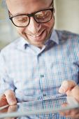 Smiling businessman in eyeglasses browsing in touchpad