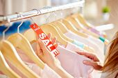 Female hand holding sale label between hangers with clothes