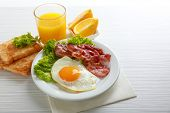 Bacon and eggs on color wooden table background