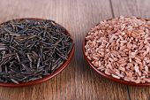 Red and black rice in pales on wooden background