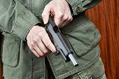 image of black-cock  - The soldier shutter cocking a pistol gun - JPG