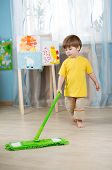 Little boy cleaning the apartment, washing floor with mop