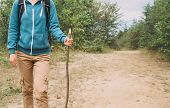 Hiker Woman Walking With A Wooden Stick In Forest