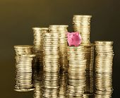 Piggy bank standing on stack of coins on brown background