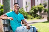 portrait of african american college boy sitting on bench
