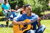 happy young african american college boy playing guitar on campus