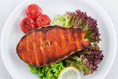 Grilled salmon  with cherry tomatoes, lettuce and lemon