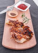 Succulent thick juicy portions of grilled fillet steak served with tomatoes  dip  on an old wooden board