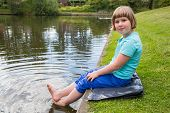 Young girl sitting with bare feet in pond