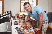 Cute pupils in computer class with teacher at the elementary school