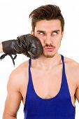 Man taking a punch with black boxing glove, isolated on white background.