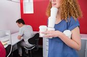 Student holding pile of coffee cup near classmate at the college