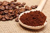 stock photo of coffee grounds  - Ground coffee on wooden scoop and coffee beans in background coffee grains - JPG