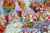 picture of lolli  - Mixed colorful candies and lolly pops on market stall - JPG