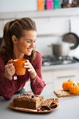 pic of home-made bread  - A woman is smiling and relaxing as she is leaning on the kitchen counter holding a cup of hot tea - JPG